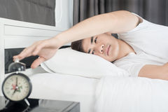 Ασιατικό άτομο που βρίσκεται στο κρεβάτι και που σταματά το ξυπνητήρι Στοκ Φωτογραφία