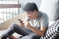 Ασιατικό άτομο που εξετάζει το τηλέφωνό του με μια έκπληκτη έκφραση Στοκ φωτογραφίες με δικαίωμα ελεύθερης χρήσης