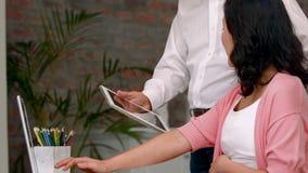 Ασιατικό άτομο που παρουσιάζει στην έγκυο ψηφιακή ταμπλέτα συζύγων του φιλμ μικρού μήκους