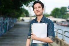 Ασιατικό άτομο που στέκεται και που κρατά το αρχείο εγγράφων στοκ φωτογραφίες με δικαίωμα ελεύθερης χρήσης