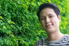 Ασιατικό άτομο που στέκεται και που παρουσιάζει ευτυχές χαμόγελό του στοκ φωτογραφίες