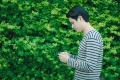 Ασιατικό άτομο που στέκεται και που χρησιμοποιεί το smartphone στοκ φωτογραφίες με δικαίωμα ελεύθερης χρήσης