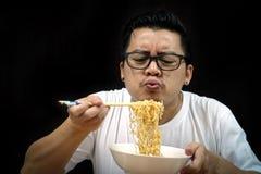 Ασιατικό άτομο που τρώει τα στιγμιαία νουντλς στοκ εικόνες
