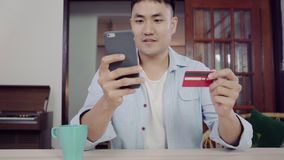 Ασιατικό άτομο που χρησιμοποιεί το smartphone για on-line να ψωνίσει και την πιστωτική κάρτα σε Διαδίκτυο στο σπίτι καθιστικών φιλμ μικρού μήκους