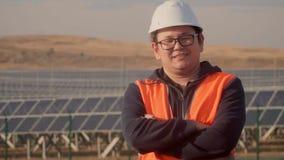 Ασιατικό άτομο σε ένα κοστούμι μηχανικών στο υπόβαθρο εγκαταστάσεων ηλιακής ενέργειας που εξετάζουν τον ορίζοντα φιλμ μικρού μήκους