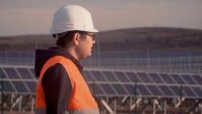 Ασιατικό άτομο σε ένα κοστούμι μηχανικών στο υπόβαθρο εγκαταστάσεων ηλιακής ενέργειας που εξετάζουν τον ορίζοντα απόθεμα βίντεο
