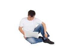 Ασιατικό άτομο στον περιστασιακό ιματισμό που κάθεται στο πάτωμα με το lap-top Στοκ Φωτογραφία