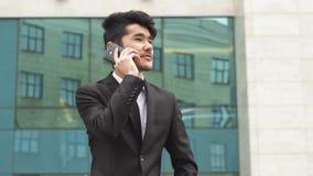 Ασιατικό άτομο στο επιχειρησιακό κοστούμι που κάνει τα τηλεφωνήματα απόθεμα βίντεο