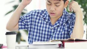 Ασιατικό αγόρι μπροστά από την εργασία στο θυμό, αγόρι στο σπίτι που κάνει την εργασία σας με το πρόσωπο στο σπίτι απόθεμα βίντεο