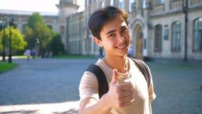 Ασιατικό αγόρι που γελά στα στηρίγματα και που παρουσιάζει όπως το σημάδι στη κάμερα, στεμένος υπαίθριος στα sunlights απόθεμα βίντεο