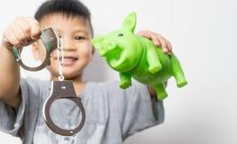 Ασιατικό αγόρι που κρατά τη piggy επιλογή τραπεζών και χειροπεδών μεταξύ της καλών εκπαίδευσης και του εγκλήματος Στοκ Εικόνες