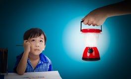 Ασιατικό αγόρι που σκέφτεται και που ανατρέχει, πλαστικό εκμετάλλευσης χεριών ηλεκτρικό Στοκ φωτογραφία με δικαίωμα ελεύθερης χρήσης