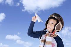 Ασιατικό αγόρι που φορά το εκλεκτής ποιότητας κράνος πτήσης που κρατά ένα έγγραφο αεροπλάνων Στοκ Εικόνα