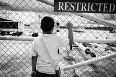 ασιατικό αγόρι λυπημένο και που στέκεται μόνο στην πόρτα του αερολιμένα α Στοκ Εικόνα