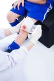 Ασιατικό αθλητικό αγόρι νεολαίας μπλε σε ομοιόμορφο κοινός πόνος μασάζ γονάτων υγείας προσοχής Στοκ εικόνα με δικαίωμα ελεύθερης χρήσης