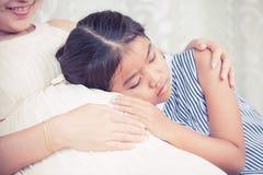Ασιατικό ακούοντας μωρό κοριτσιών παιδιών και αγκάλιασμα της έγκυου μητέρας Στοκ Φωτογραφίες