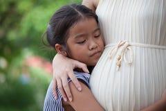 Ασιατικό ακούοντας μωρό κοριτσιών παιδιών και αγκάλιασμα της έγκυου μητέρας Στοκ Εικόνα