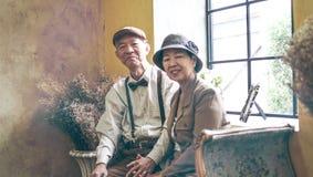 Ασιατικό ανώτερο εκλεκτής ποιότητας αναδρομικό ύφος φορεμάτων χαμόγελου ζευγών στην πολυτέλεια Στοκ Εικόνα