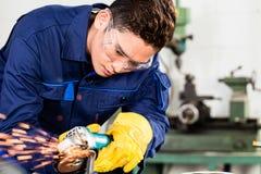 Ασιατικό αλέθοντας μέταλλο εργαζομένων στις εγκαταστάσεις κατασκευής στοκ εικόνες