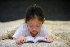 Ασιατικό βιβλίο ανάγνωσης παιδιών στο κρεβάτι Στοκ Εικόνα
