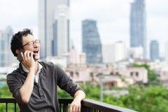 Ασιατικό γέλιο ομιλίας ατόμων στη δυνατή χαλάρωση χαμόγελου smartphone έξω στο μπαλκόνι με το διαστημικό υπόβαθρο αντιγράφων άποψ στοκ εικόνες με δικαίωμα ελεύθερης χρήσης