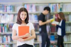 Ασιατικό γυναικείο χαμόγελο σπουδαστών και διαβασμένος ένα βιβλίο στη βιβλιοθήκη Στοκ Εικόνες