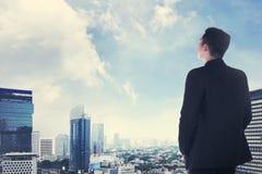 Ασιατικό επιχειρησιακό άτομο που φαίνεται η πόλη από τη στέγη Στοκ Φωτογραφία