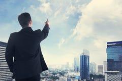 Ασιατικό επιχειρησιακό άτομο που φαίνεται η πόλη από τη στέγη Στοκ Εικόνες