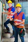 Ασιατικό ελέγχοντας να στηριχτεί εργαζομένων στο εργοτάξιο οικοδομής Στοκ εικόνες με δικαίωμα ελεύθερης χρήσης