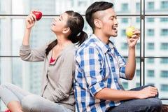 Ασιατικό ζεύγος που έχει τα μήλα ως υγιές πρόχειρο φαγητό Στοκ Εικόνα