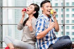 Ασιατικό ζεύγος που έχει τα μήλα ως υγιές πρόχειρο φαγητό Στοκ εικόνα με δικαίωμα ελεύθερης χρήσης