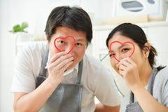 Ασιατικό ζεύγος που κρατά τις κόκκινες καρδιές Στοκ εικόνα με δικαίωμα ελεύθερης χρήσης
