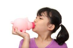 Ασιατικό κατσίκι που φιλά τη piggy τράπεζα Στοκ εικόνα με δικαίωμα ελεύθερης χρήσης