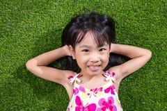 Ασιατικό κινεζικό μικρό κορίτσι που βρίσκεται στη χλόη στοκ εικόνες