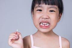 Ασιατικό κινεζικό μικρό κορίτσι που κρατά το ελλείπον δόντι της Στοκ Εικόνες
