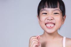 Ασιατικό κινεζικό μικρό κορίτσι που κρατά το ελλείπον δόντι της Στοκ φωτογραφία με δικαίωμα ελεύθερης χρήσης