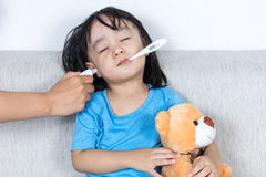 Ασιατικό κινεζικό μικρό κορίτσι που παίρνει τη μέτρηση αυτιών για temp πυρετού Στοκ Φωτογραφίες
