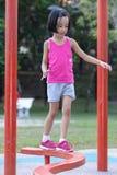 Ασιατικό κινεζικό μικρό κορίτσι που περπατά στην ακτίνα ισορροπίας στοκ φωτογραφίες