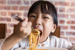 Ασιατικό κινεζικό μικρό κορίτσι που τρώει τα μακαρόνια bolognese στοκ φωτογραφία