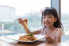 Ασιατικό κινεζικό μικρό κορίτσι που τρώει τα μακαρόνια bolognese Στοκ Φωτογραφίες