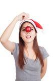 Ασιατικό κορίτσι με το κόκκινο μπιχλιμπίδι λαβής καπέλων santa στη μύτη της στοκ εικόνες