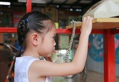 Ασιατικό κορίτσι παιδιών που μιλά στο αναδρομικό τηλέφωνο στοκ φωτογραφία με δικαίωμα ελεύθερης χρήσης