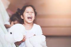 Ασιατικό κορίτσι παιδιών που γελά και που έχει τη διασκέδαση που παίζει με το κάλυμμα Στοκ Φωτογραφία