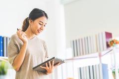 Ασιατικό κορίτσι που απασχολείται στο σπίτι στο γραφείο που χρησιμοποιεί την ψηφιακή ταμπλέτα, με το διάστημα αντιγράφων Επιχειρη στοκ εικόνα