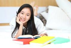 Ασιατικό κορίτσι που διαβάζει ένα βιβλίο στο κρεβάτι, που βρίσκεται στο χαμόγελο στομαχιών της ευτυχές και που χαλαρώνουν μια ημέ Στοκ Εικόνες