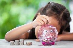 Ασιατικό κορίτσι που κάνει τους σωρούς των νομισμάτων και που βάζει τα χρήματα στη piggy τράπεζα στοκ εικόνες