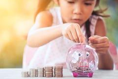 Ασιατικό κορίτσι που κάνει τους σωρούς των νομισμάτων και που βάζει τα χρήματα στη piggy τράπεζα στοκ εικόνα με δικαίωμα ελεύθερης χρήσης