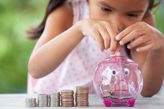 Ασιατικό κορίτσι που κάνει τους σωρούς των νομισμάτων και που βάζει τα χρήματα στη piggy τράπεζα στοκ φωτογραφία με δικαίωμα ελεύθερης χρήσης