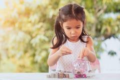 Ασιατικό κορίτσι που κάνει τους σωρούς των νομισμάτων και που βάζει τα χρήματα στη piggy τράπεζα στοκ φωτογραφία