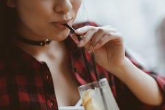 Ασιατικό κορίτσι που πίνει latte με το άχυρο στον καφέ, που έχει την έννοια μεσημεριανού γεύματος Στοκ φωτογραφία με δικαίωμα ελεύθερης χρήσης